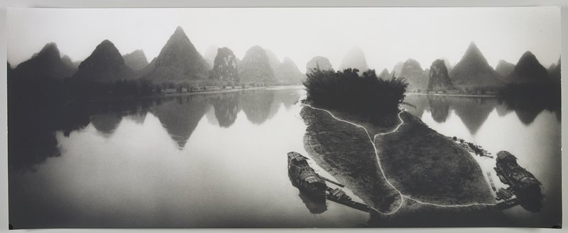 small island with 2 medium-sized boats at either side and numerous small boats on R side; foliage at back of island; triangular land formations on opposite band in background; Li River, Peoples Republic of China