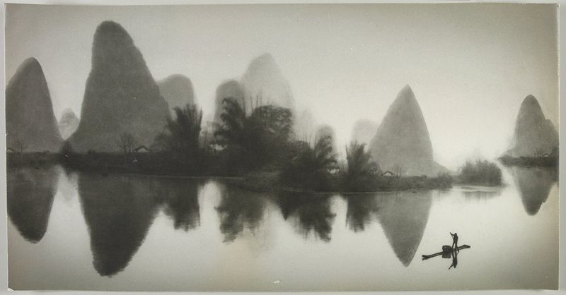 standing figure rowing a boat at LRC; tall land forms reflected in water with trees and partially hidden buildings on opposite bank; Peoples Republic of China