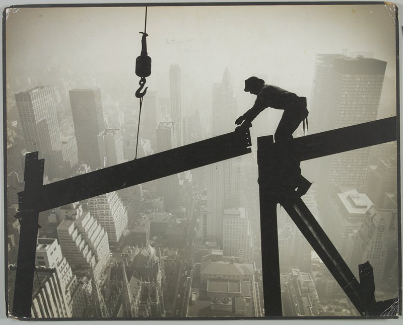 man standing on a steel beam above a city, pulling a beam on a large hook into place