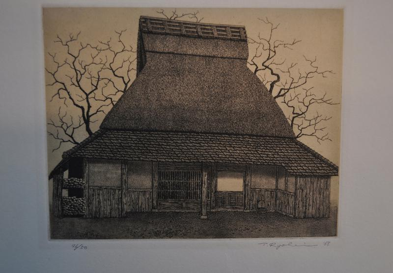 thatch-roofed building with bare trees