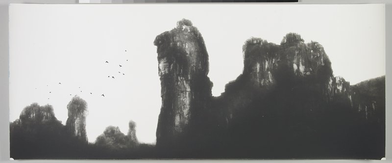 large rock formation at R, with 2 similar formations in distance at L; small flock of flying birds at L; Li River, Peoples Republic of China