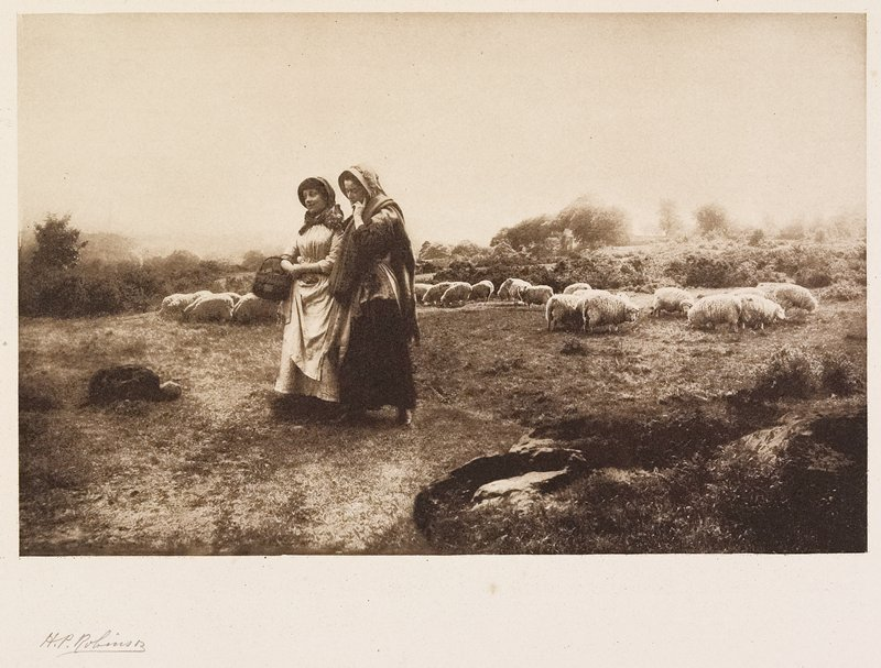 2 women wearing bonnets and walking side by side through a field with sheep in background; from a portfolio with essay on the photographer