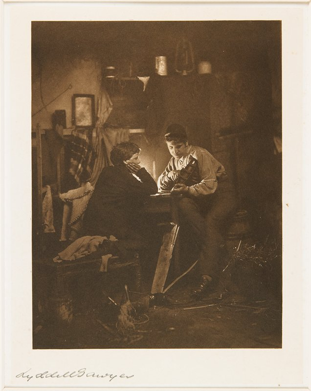 2 young men seated opposite each other at a small table; man at R holds a small model boat; from a portfolio with essay on the photographer
