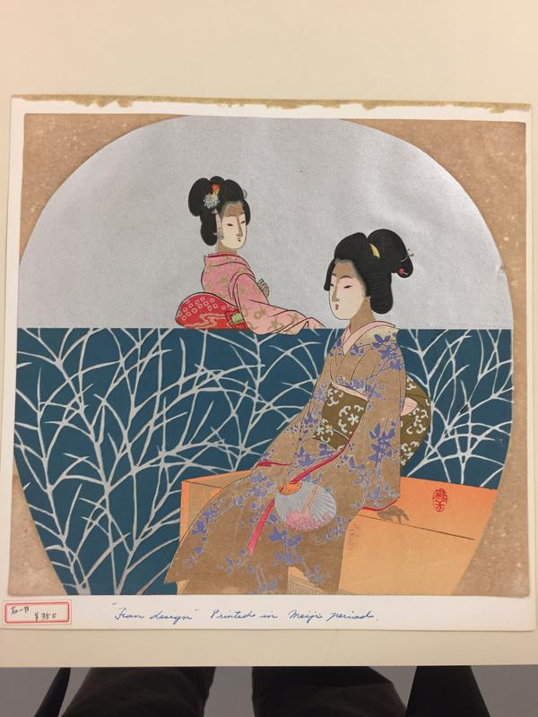 seated young woman in foreground wearing tan and purple flowered kimono; young woman in tan and pink kimono at left, resting her PR arm on a short turquoise wall with silver branch design