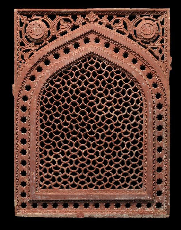 reddish carved openwork stone; central arch with wide border with open stars; top corners contain rosettes on one side and 'Allah' on the other; central trellis design of curving lines; attached to mount