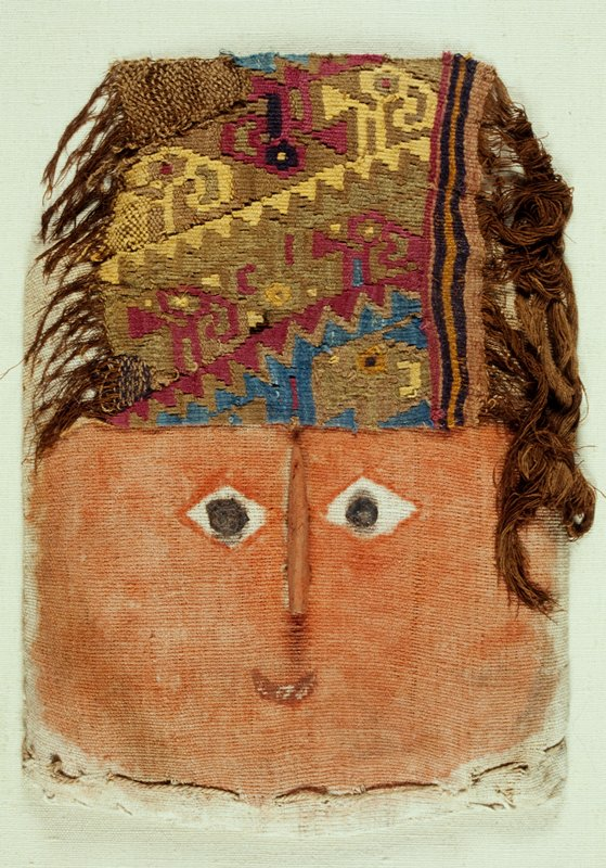 square-shaped face made of stuffed cloth; woven multi-colored headband with geometric shapes and hairlike brown fringe; face painted orange with small red smiling mouth; disk-shaped wood irises and wedge-shaped protruding nose; mounted inside a plexi case