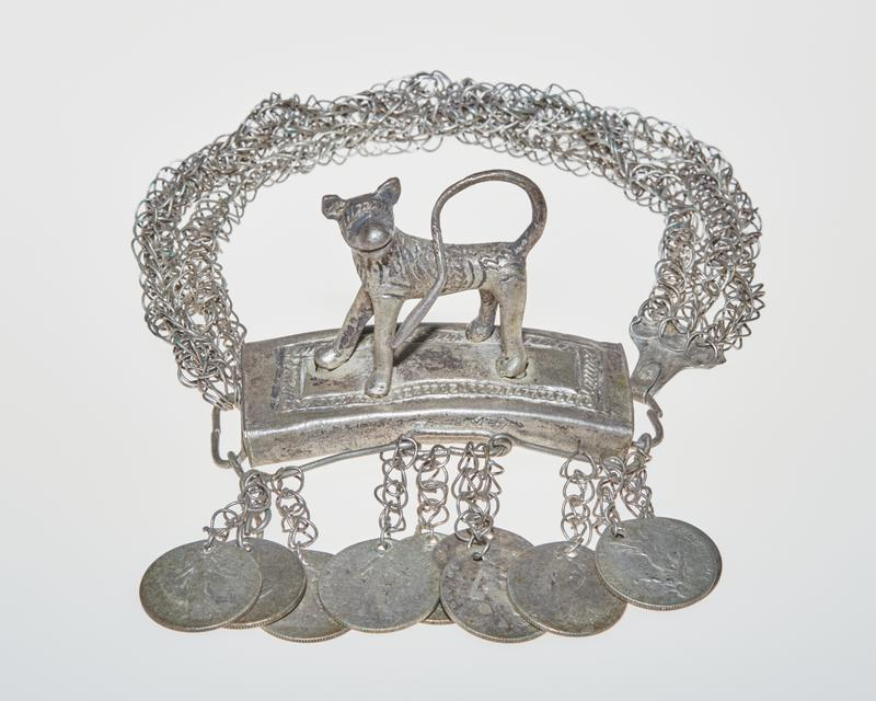 three looped chains attached to ring on base of curved platform and hooked to ring on other side; four legged animal with pointed ears stands on platform with tail curled over back, facing front left; patterning and details carved on animal and on top of platform; 10 50 centimes coins hanging from wires around platform on looped chains (one set of four and two sets of three); all coins have a figure surrounded by text on one side and a branch of leaves with text on the other