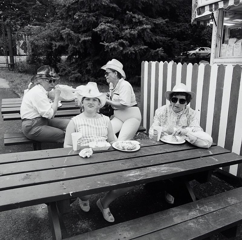 elderly woman wearing sunglasses and a hat, and girl wearing a cowboy hat and tank top, seated at a picnic table in front; 2 women wearing cowboy hats and sunglasses seated sideways at a picnic table behind