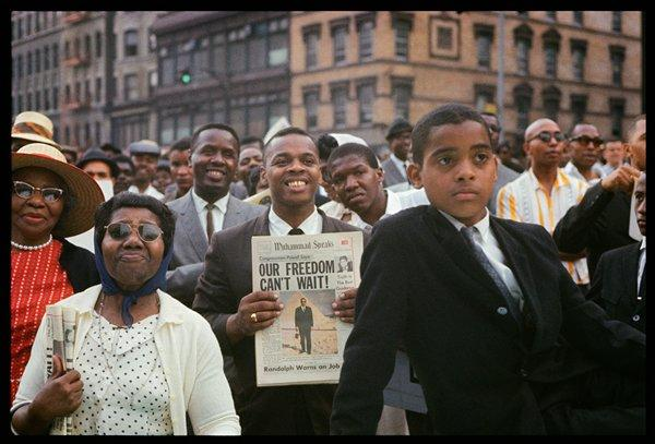 "color image of a group of Black people with tall buildings in background; boy wearing a dark suit at right; smiling man at center holding a newspaper (""Muhammad Speaks"") with the headline, ""OUR FREEDOM CAN'T WAIT!""; two women at left wearing sunglasses; received in black frame"