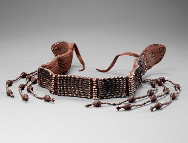belt; reddish-brown overall; blue and white beaded designs on each leather end with cross and triangle motifs; rectangular sections of tight rows of silver metal faceted beads separated by bands of white beads; three-stand silver beaded tassels/dangles at either end with brown ovoid nuts or seeds; encrusted with reddish pigment accretions overall