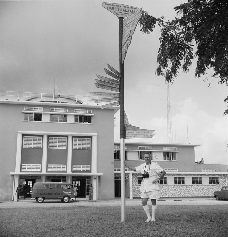 Black and white image of a man standing below a sign with the distances to different places on it