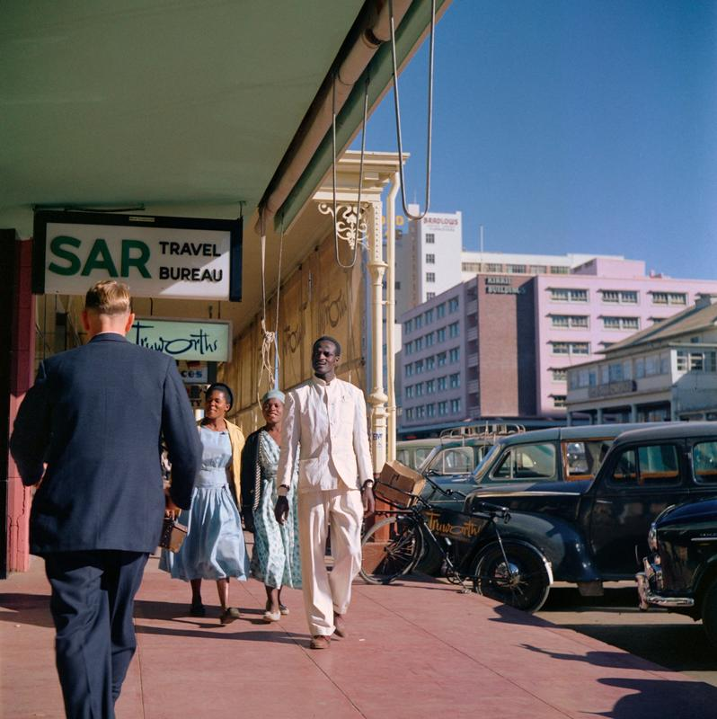"""Color image of figures walking down a covered sidewalk; cars parked along R side; sign over man's head says """"SAR"""""""