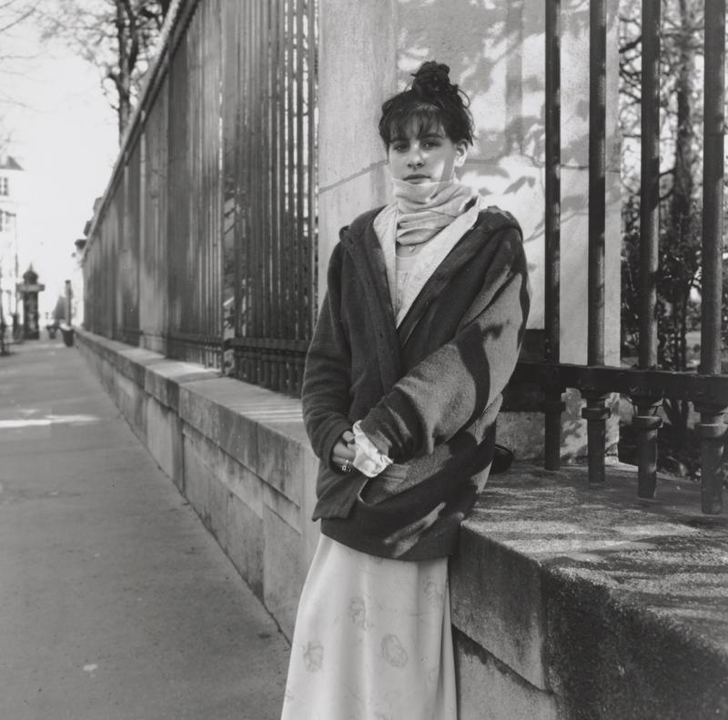 black and white image of a young woman with her hair in a bun wearing a scarf, oversized sweater and skirt against a short wall with a wrought iron fence above it