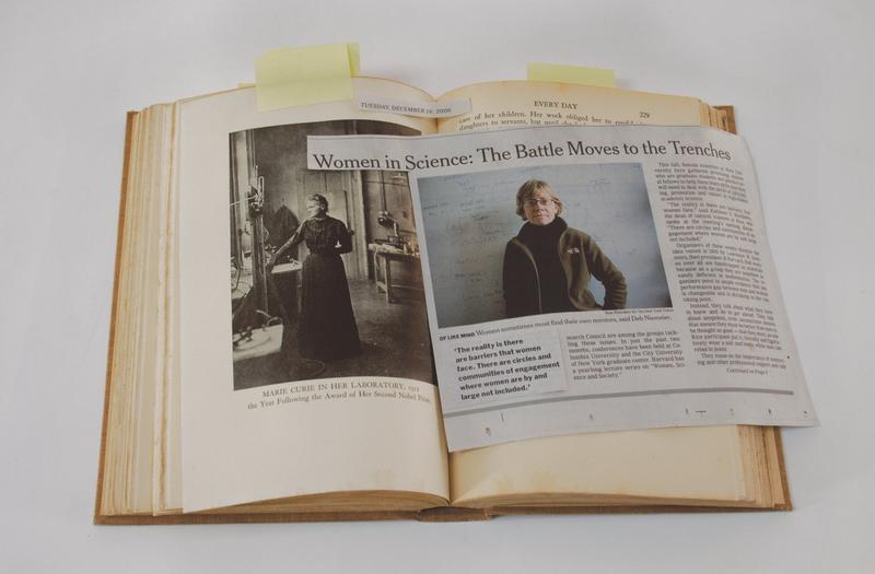 "color image of a newspaper clipping with a photo of a woman wearing glasses and an olive-colored jacket under the headline, ""Women in Science..."", on top of a book with a photograph of Marie Curie in her lab"