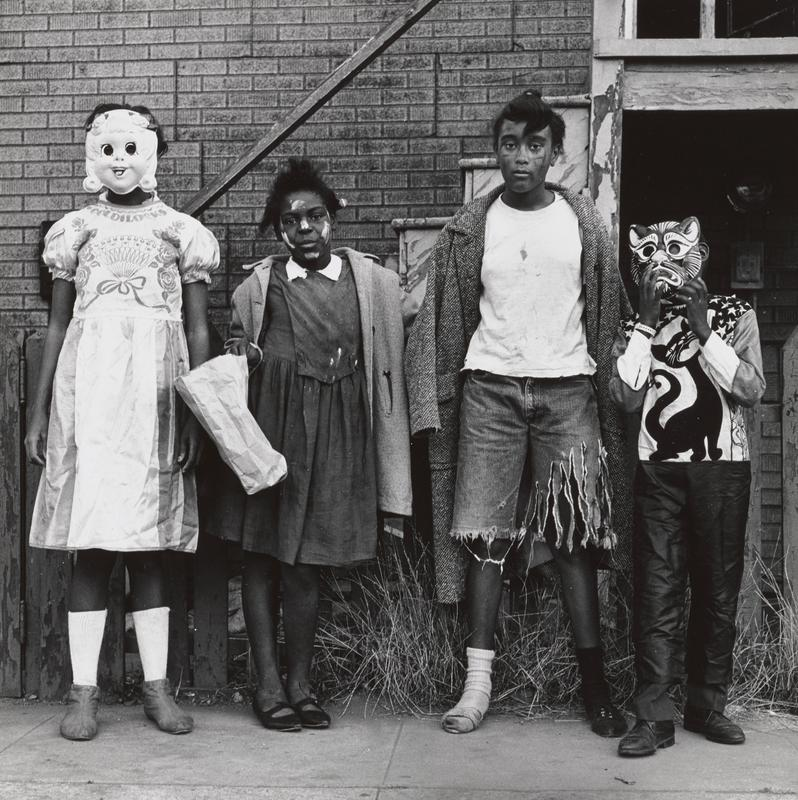 four children in front of a building in Halloween costumes; girl at left wears Goldilocks costume with a mask; boy at right wears a cat mask and a shirt with a cat on the front