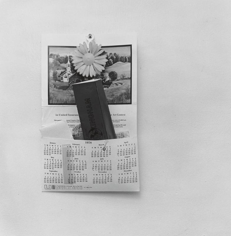 black and white image of a 1978 wall calendar with a pocket with papers inside and a picture of a landscape with a church; daisy ornament hanging over picture on calendar