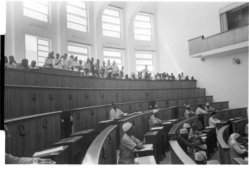 Black and white image of people sitting in a room with semi-circular walls and desks