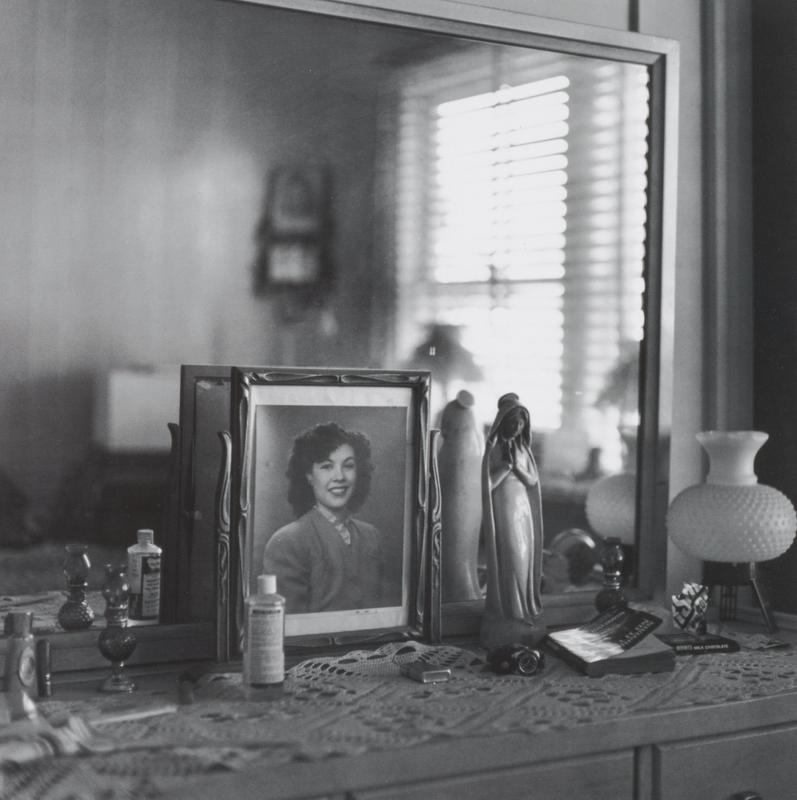 black and white image of a dresser with a mirror; framed photograph of a woman; standing figurine of Mary; lamp with rounded shade