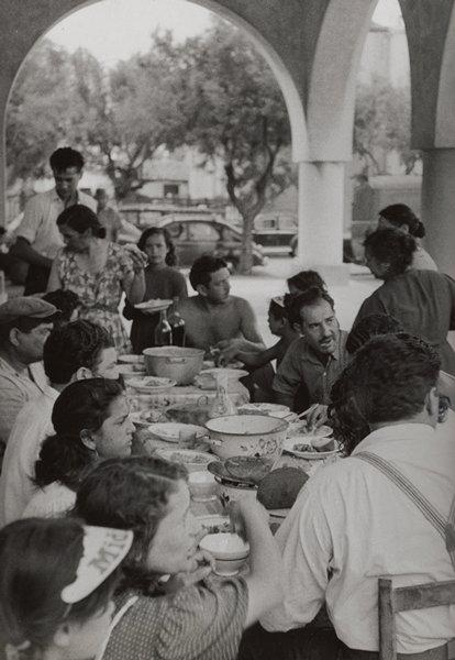 black and white image of a group of people seated at a table, eating; girl in LRC wearing a visor; five standing figures; archway with cars and trees in background