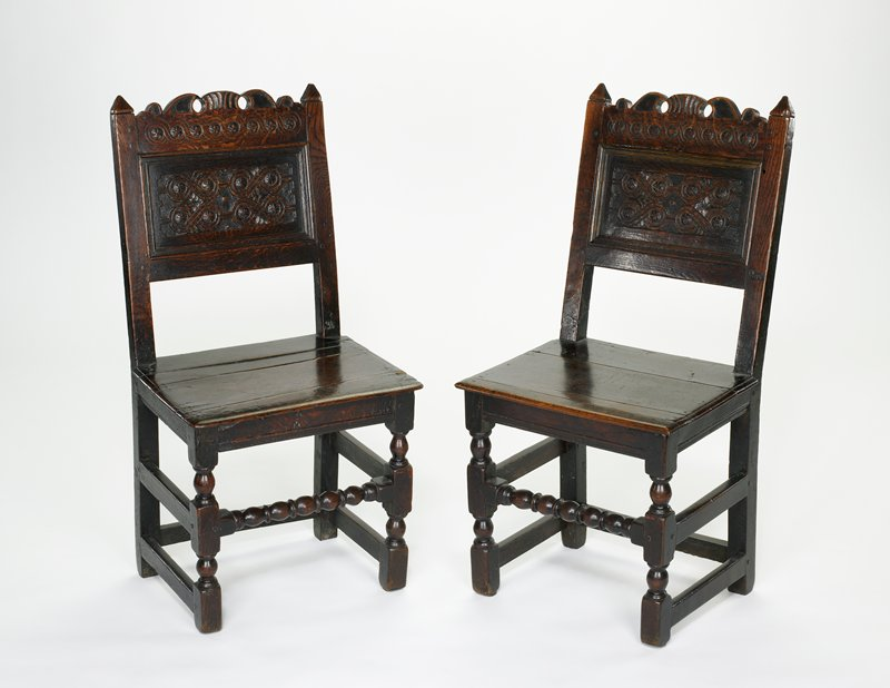 Chair, yorkshire type with carved back, top rail and simple cresting; turned legs and stretcher; oak; front stretcher turned. one of a pair (23.26.1)