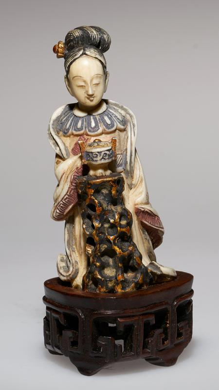 carved figure with incense burner on stand