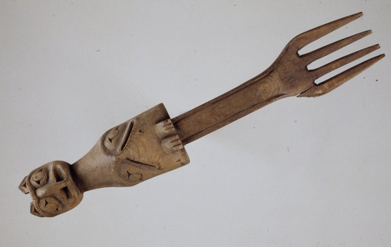 fork with four broad prongs and carved handle. It represents on top a head of a hawk with its beak turned down over a human mouth and ears on top to indicate it is an animal, and below another bird with very small beak resembling an owl. On the back are carved the tails of the birds, and below the lower head are its feet.