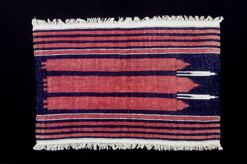 Coarsely woven mat with bands at top and bottom of red and dark blue ad, in the center, three wide red stripes on a blue ground. Finished at top and bottom with white warp fringe.