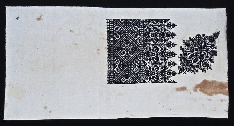 Black silk emboridery on linen. Evidently a practice piece showing portion of border and diamond shaped unit used for corner decoration. Pattern typical of the embroideries made in the city of Fez. Similar to 30.23.15. Brown stains on linen.