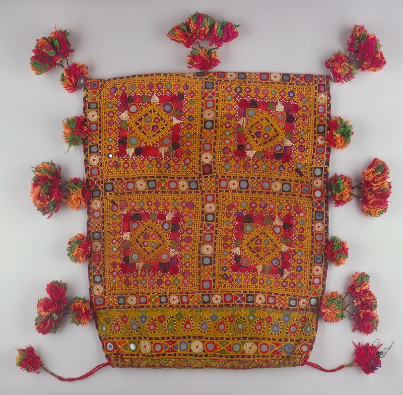 Square pouch of purple cotton material fastened at top with draw strings. Embroidered and encrusted with mirrors. Ornamented at sides and bottom with bunches of tassels.