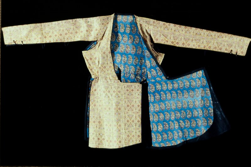 Woman's Tunic of yellow brocade with all-over floral pattern in different colors. Lined with blue printed cotton. The sleeves are open - being held together under the arm by black tapes - and near the cuff by metal buttons. Metal brocade.