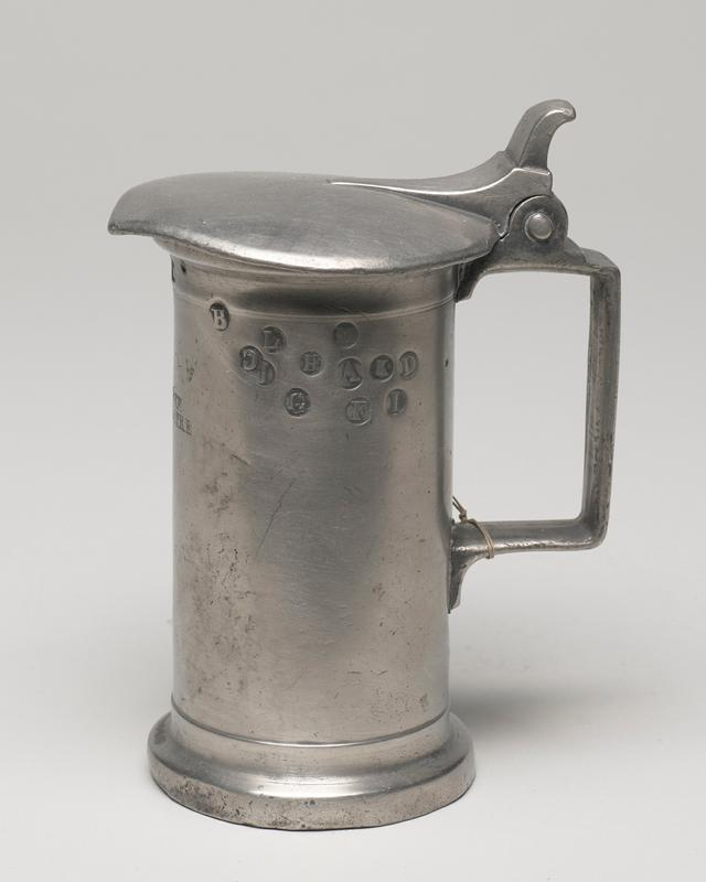 wine measure with square handle and heart-shaped cover protruding over lip