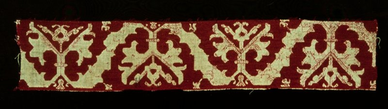 border, natural color linen, embroidered in red diagonal and straight stitch in a very conventionalized design of leaves and flowers; the veins of the leaves done in feather stitch