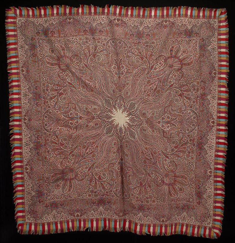 kussaba, or square shawl (double); one side is white while other has blue ground; completely covered with floral, leaf and arabesque design; many pieces have been woven separately and incorporated into the whole; the border, woven separately and added, is covered with flowers and floral trees; much of the design is outlined in embroidered stitch; outer border of strips of fringed colored woolen with flowers woven into top