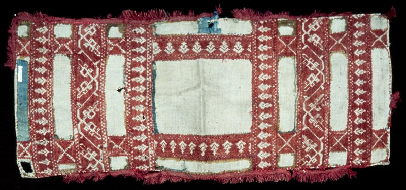 border, linen, embroidered in red silk in a design of strips alternating with linen which at one time must have been covered with green silk, bits of which remain; the edges are finished with red braid, some of which has been torn off; there are several holes in the piece