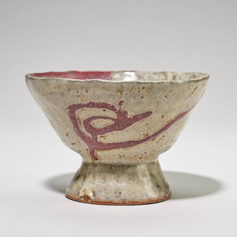 Bowl, on foot heavy gray glaze with character in purple on one side.