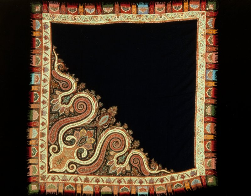 shawl, embroidered, of the Kusaba or square type. the field is black, of the so-called twill weave, and the principal designs, cut from variously colored shawl cloths, are either inserted or applied, and are joined to the main body of the shawl by such skillful embroidery that it is almost impossible to detect. A brilliant border surrounds the entire square. Red, white and turquoise blue are the predominating colors, combined with shades of yellow, green, and rose. The design is the well known Kashmir butha or flower motif with variations. Wool.