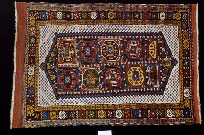 Hearth rug, Yomud type. A white field sewn with small stars (?) ('checkerboard') contains a badly designed hexagonal medallion, which in turn contains ten octagon shapes in various colors. The hearth field is enclosed by a reciprocal sawtooth band in three shades. Three borders, the main one made up of geometric single flowers divided by three triangles laid end to end. Ends-narrow web with loose warp threads. Sides-over cast with different colored yarns. Ghiordes knot.