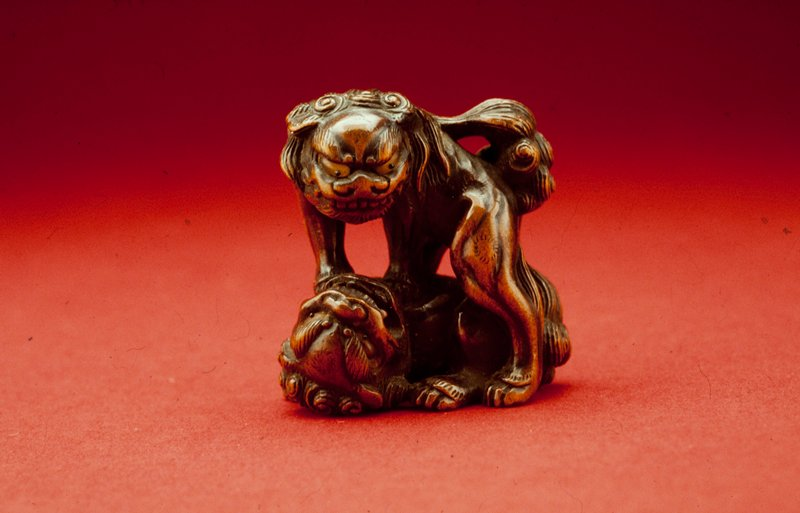 netsuke, in form of pair of grotesque lions with amber (?) eyes, playing together