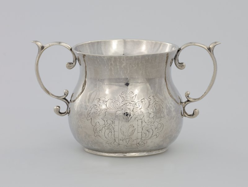 caudle cup with bulbous circular body flaring at the rim; engraved with a coat-of -arms composed of a shield charged with a double headed eagle (probably those of Brown or Browne of Massachusetts); two graceful open scrolled handles