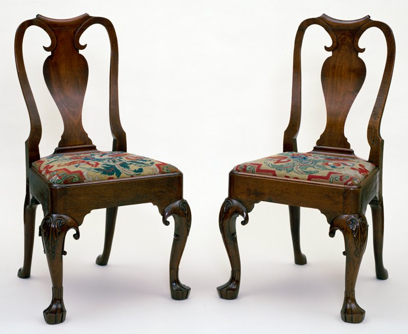 chairs, pair of, with fiddle backs; cabriole legs, the knees carved with a simple leaf design; Dutch grooved feet; slip seats upholstered in old wool needlework in shades of red and bright yellow cross stitch