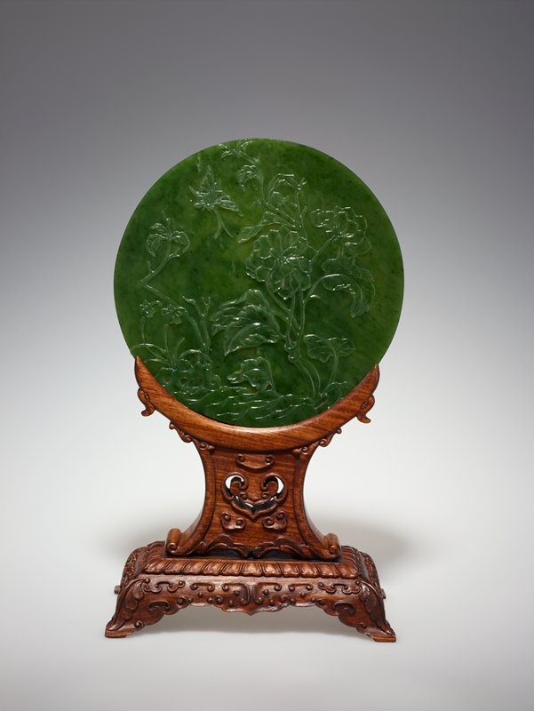 Disc, one of a pair, spinach green jade, carved on both sides with designs of birds and flowers. Discs of this type, probably inspired by the ancient PI discs, were used for altar or table decorations. Alternate title Circular Table Screen with Stand Stand for this piece is in A10.8 MS; Labelled 34.21.3b Pair is 34.21.3