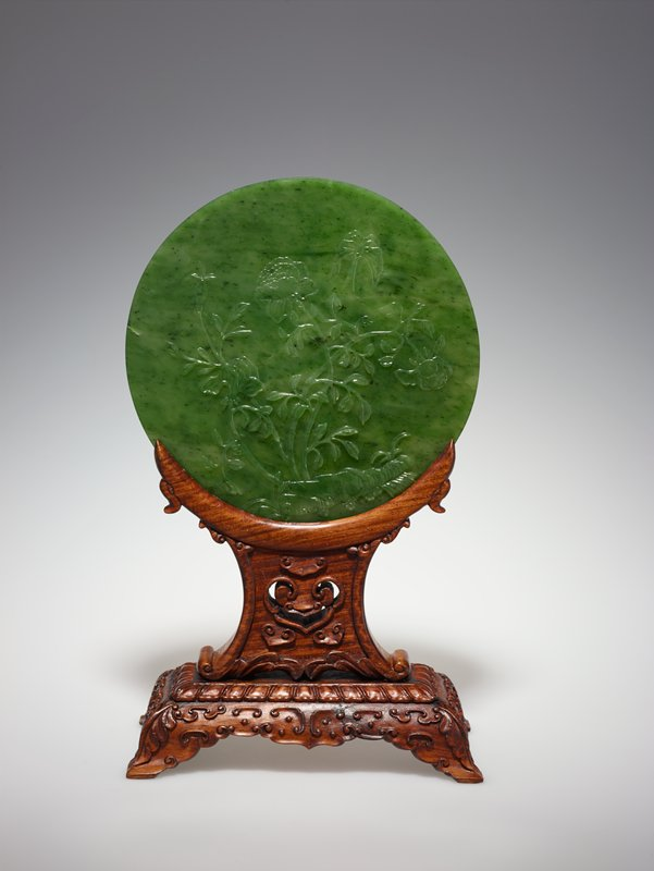 Disc, one of a Pair, spinach green jade, carved on both sides with designs of birds and flowers. Discs of this type, probably inspired by the ancient PI discs, were used for altar or table decorations. Alternate title Circular Table Screen with Stand Stand for this piece is in A10.8 MS; Labelled 34.21.3b Pair is 34.21.2
