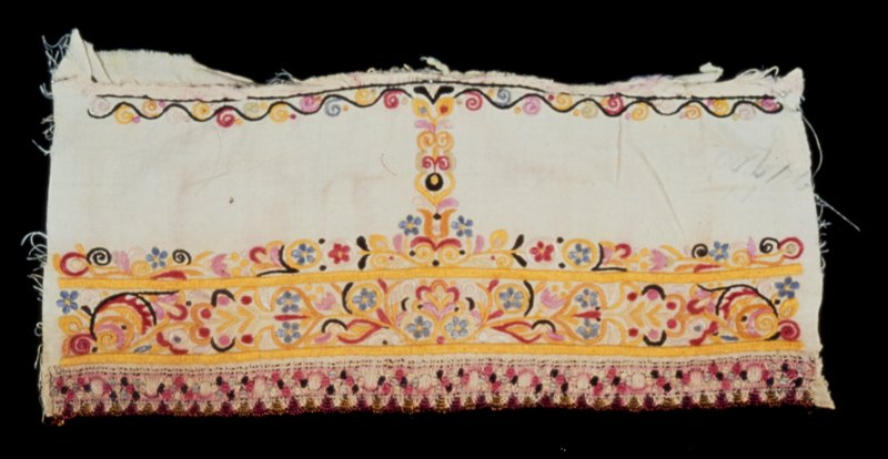 piece from sleeve, embroidered in colors, principally yellow wiwth a band of colored lace on the hem; the wide border of floral designs is connected by a strip of embroidery with the narrow scroll border