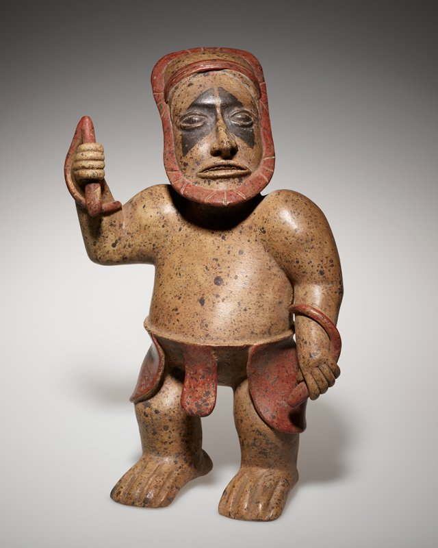 Standing male figure, with whip handle in proper right arm wrapping around behind back to proper left arm. Whip, outline of head, and garment around figures waist are red. Black diamond shapes over each eye.
