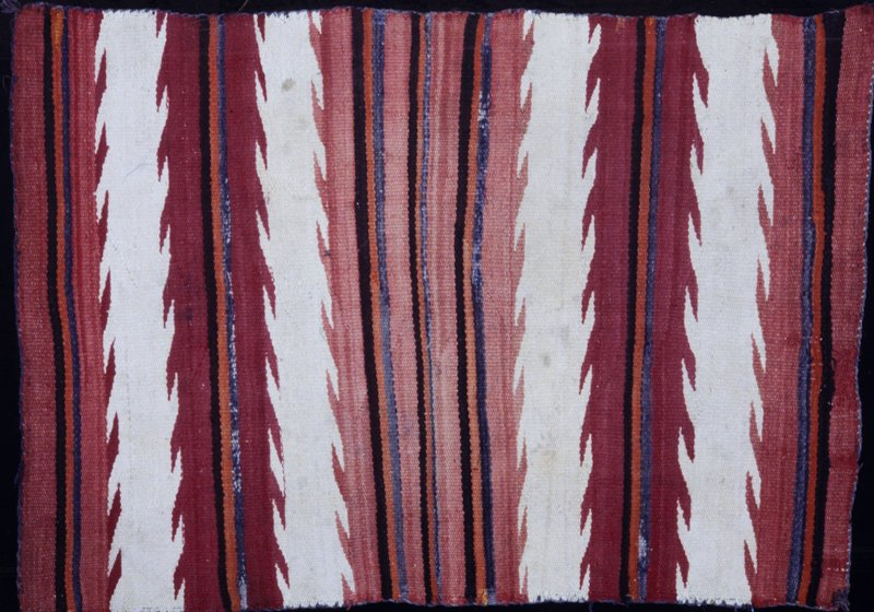 rug, Navajo, with deep horizontal zigzag stripes in shades of rose and white, banded with narrow stripes in blue, orange, dark brown, and gray; edges overcast with grey yarn
