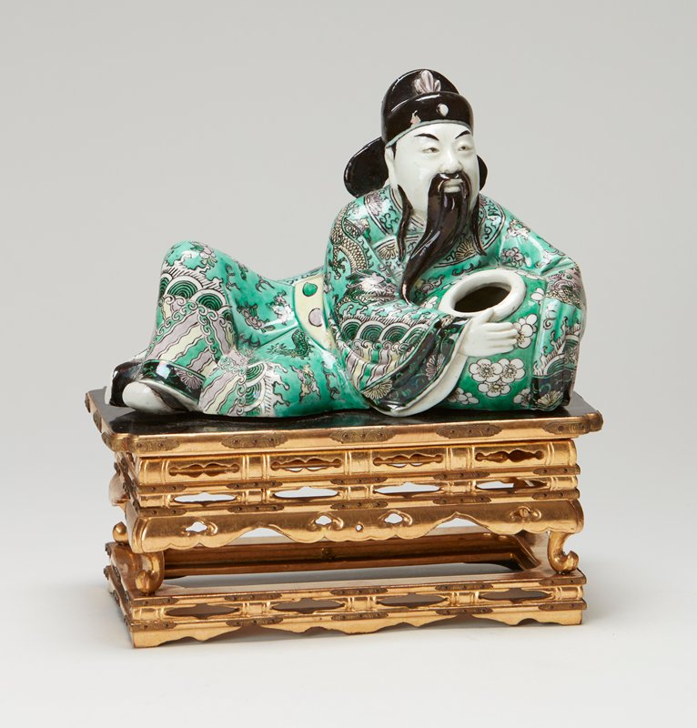 Reclining figure of geinty holding a bowl in crook of arm. Black flat cap with high arched half-crown and two flaring tabs projecting over shoulders in back. Long black mustachios and beard. Five color porcelain, apple green ground, gilt lacquer stand.