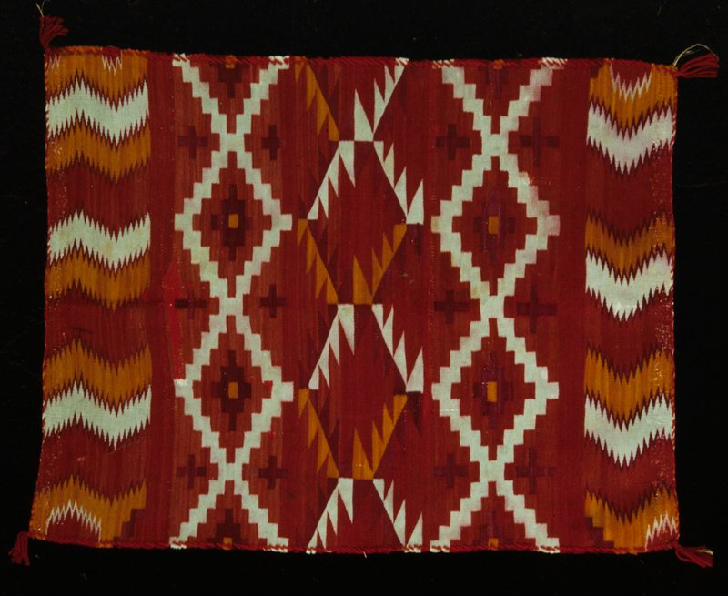 rug, finely woven in a design of interlocking stepped and sawtooth medallions in shades of red, ranging from brilliant orange to purple and white; end borders carry band of reciprocal zigzag stripes with sawtooth edges; edges overcast with red wool