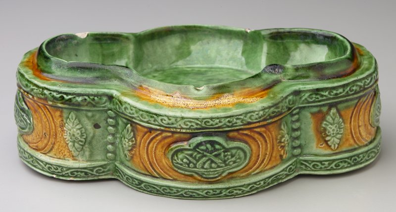 quadrilobed design; edges decorated with applied stamped scroll and floral designs; green and tan glaze