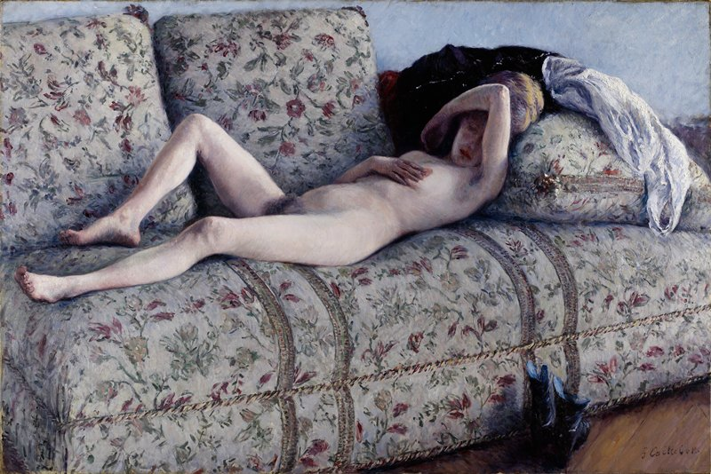 Nude female figure lying on a flowered couch