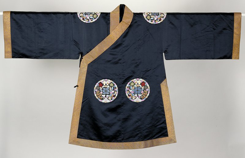 Outer Coat of black satin with seven applied medallions embroidered in satin stitch with the Twelve Ancient ornaments in shades of blue, lavender, pink, brown, red, green, tan and yellow. All around a border of gold and bright blue brocade in cloud pattern. Coat slit at sides and lined with thin blue silk. Mrs. Harris notes This coat especially made for Yuan Shi Kai, first President of the Chinese Republic, who had ambitions of becoming Emperor. He was prevented only by leaders of the Chinese Republic.